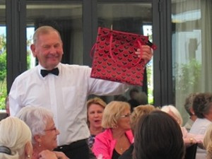 "Trustee Neville Dippie holding one of the donated bags being auctioned at the Trust's ""Old Bag's Lunch"" fundraiser"