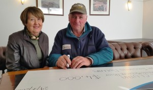 Robert Duncan signs the cheque for $4,000 - adding to the $2,000 already raised_media
